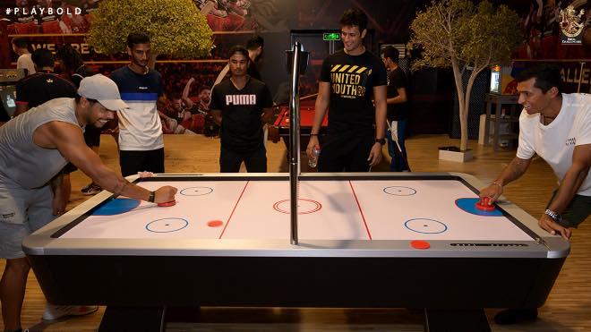 RCB teammates enjoying air hockey at the team recreation centre